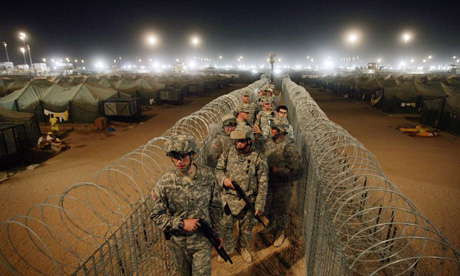 Shotgun-wielding US troops walk along a corridor separating detainees at Camp Bucca in Iraq. Photograph: David Furst/AFP/Getty Images