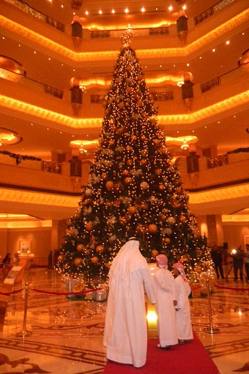 Locals admire the 46-foot artificial tree erected in the lobby of the Emirates Palace hotel in Abu Dhabi. The hotel bedecked the tree in $11 million dollars worth of jewelry.  Photo courtesy of WSJ/Nour Malas.