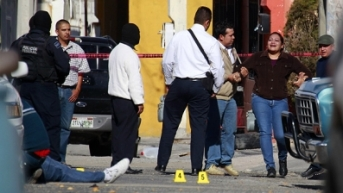 Dec. 14: A woman is held back by police as she reacts while seeing a relative dead lying on the ground after he and another man were killed by gunmen in the northern border city of Ciudad Juarez, Mexico.  Photo courtesy AP