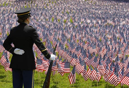A member of a military Honor Guard stands at parade rest during a Memorial Day remembrance at the Soldiers and Sailors Monument on the Boston Common in Boston, Thursday morning, May 26, 2011. Ten thousand American flags have been place near the monument to represent the number of Massachusetts citizens who have given their lives in America's wars. (AP Photo/Stephan Savoia)