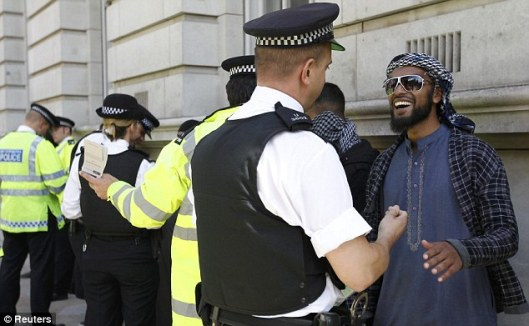 Stop and search: Police officers with a group of Muslim protesters near Downing Street today