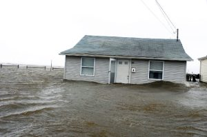 A wave crashes against a home on the Great South Bay, Long Island, NY.  Credits: Christie Farriella for NYDN