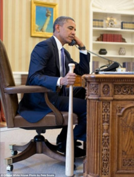 Batter up! President Obama talks on the phone with Prime Minister Recep Tayyip Erdogan of Turkey in the Oval Office on July 30.  Courtesy of DailyMail.co.uk.