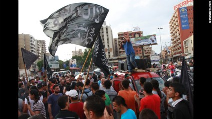 """Protesters carry flags that read """"There is no God but Allah, Mohammed is Allah's messenger"""" and chant slogans during a protest against a film they consider blasphemous to Islam and insulting to the Islamic prophet in Tripoli, Lebanon, on Thursday."""