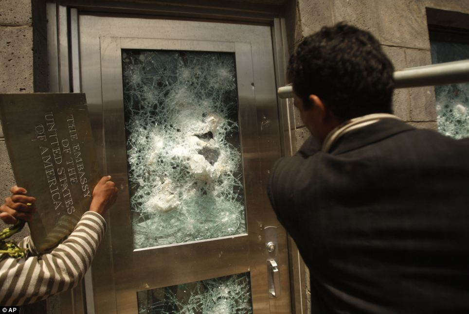 Yemeni protestors break a door of the US Embassy with a pole after ripping off the metal plaque.  Image courtesy of the DailyMail.co.uk.