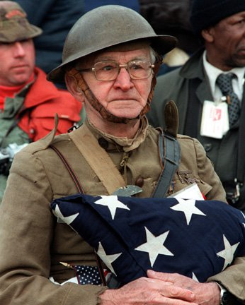 Joseph Ambrose, an 86-year-old World War Iveteran, attends the dedication day parade for the Vietnam Veterans Memorial in 1982, holding the flag that covered the casket of his son, who was killed in the Korean War.  Wikipedia.