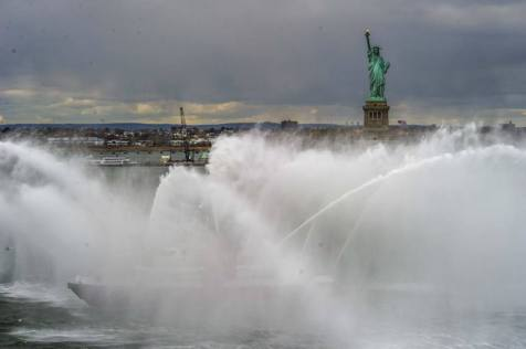 004 - 131108-N-UE577-225 NEW YORK CITY (Nov. 8, 2013) - Amphibious transport dock ship USS New York (LPD 21) is honored by a water cannon display as she passes the Statue of Liberty in transit to New York City. New York departed Naval Station Norfolk to conduct training and participate in Veterans Week New York City to honor the service of our nation's veterans. (U.S. Navy photo by Mass Communication Specialist 2nd Class Andrew B. Church/RELEASED)