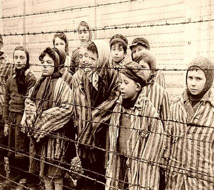 Photograph No. 66935A: Child survivors of Auschwitz, wearing adult-size prisoner jackets, stand behind a barbed wire fence. Among those pictured are Tomasz Szwarz; Alicja Gruenbaum; Solomon Rozalin; Gita Sztrauss; Wiera Sadler; Marta Wiess; Boro Eksztein; Josef Rozenwaser; Rafael Szlezinger; Gabriel Nejman; Gugiel Appelbaum; Mark Berkowitz (a twin); Pesa Balter; Rut Muszkies (later Webber); Miriam Friedman; and twins Miriam Mozes and Eva Mozes wearing knitted hats. STILL PHOTOGRAPH FROM THE SOVIET FILM of the liberation of Auschwitz, taken by the film unit of the First Ukrainian Front. Image courtesy of Wikimedia Commons.  Released into the public domain by its author, United States Holocaust Memorial Museum, courtesy of Belarussian State Archive of Documentary Film and Photograph.